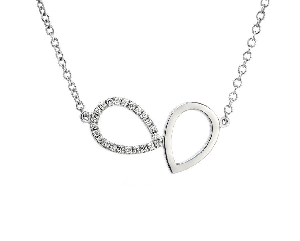 """Lumier colgante B 1  Producto <span style=""""font-weight: 400;"""">Dos gotas enlazadas de oro blanco cubiertas por 21 diamantes corte brillante que suman 7 puntos en total.</span>"""