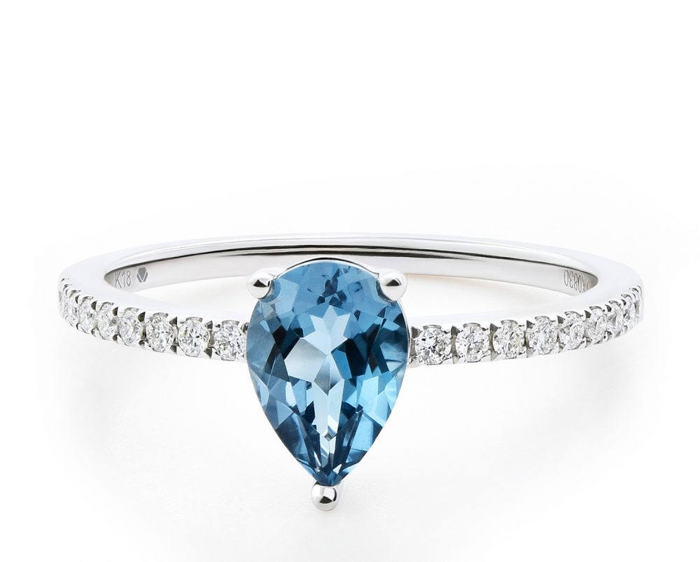 Solitario Naim Oro Blanco 18k, con 1 Topacio pera 85 pt, 18 Diamante brillante que suman 10 pt