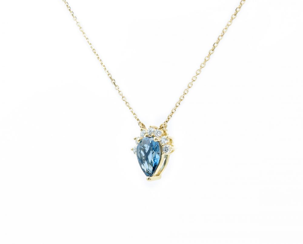 Collar Aidan Blue Oro Amarillo, o Blanco 18k, con 1 Topacio London Blue pera que suman 95 pt, más 7 Diamantes brillante que suman 14 pt, más 1 Cadena Tamaño: 11x11mm